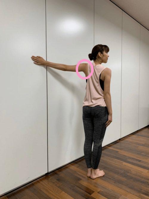 手のひらを壁に付けて肩のストレッチ(後ろからの見た目)